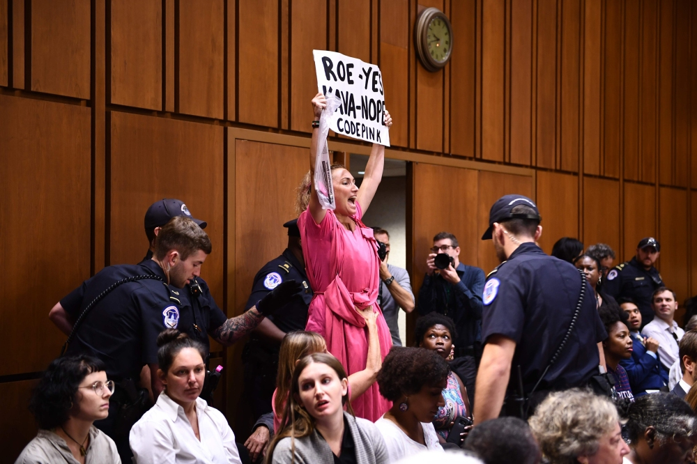Image: A member of Code Pink protests as Supreme Court nominee Brett Kavanaugh arrives