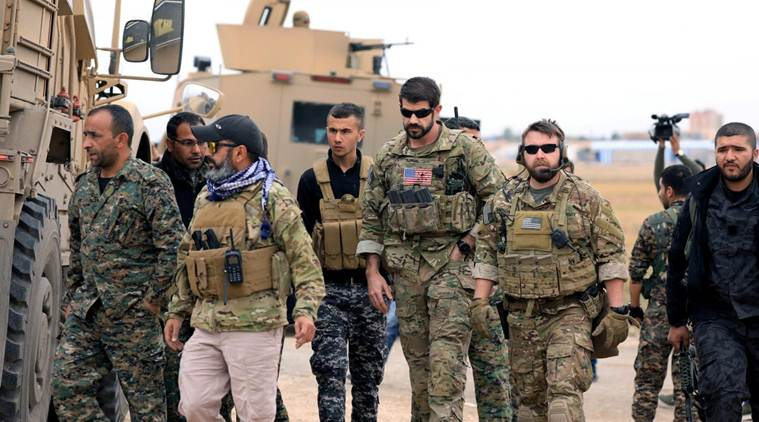 FILE PHOTO: Syrian Democratic Forces and U.S. troops are seen during a patrol near Turkish border in Hasakah